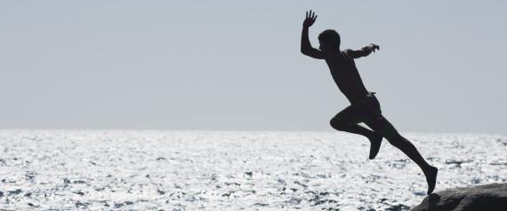 Teenage boy jumping into ocean, silhouette