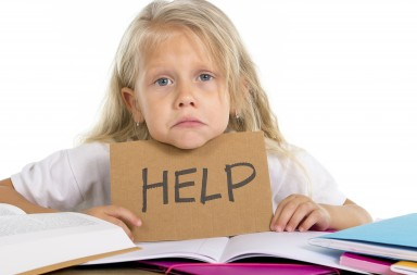 sweet little schoolgirl holding help sign in stress with homework