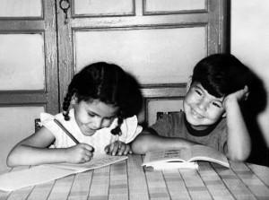 Niños de parvulario realizan en sus cartillas los deberes mandados por el maestro en un colegio de Badajoz, en septiembre de 1966. EFE