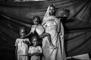 Magbola Alhadi, de 20 años, y sus tres hijas posan para un retrato en el campo de refugiados de Jamam en el condado de Maban, Sudán del Sur, el 11 de agosto de 2012. Magboola y su familia resistieron bombardeos aéreos durante varios meses, pero decidieron que era hora de abandonar su pueblo de Bofe la noche en que los soldados llegaron y abrieron fuego. Con sus tres hijas, viajó durante 12 días desde Bofe hasta la ciudad de El Fudj, en la frontera del sur de Sudán. La cosa más importante que Magboola pudo traer con ella es la cacerola que sostiene en esta fotografía. No era la olla más grande que tenía en Bofe, pero era lo suficientemente pequeña para viajar con ella, y lo suficientemente grande como para cocinar sorgo para ella y sus tres hijas (de izquierda a derecha: Aduna Omar, 6, Halima Omar, 4, Y Arfa Omar, 2) durante su viaje. Foto © Brian Sokol. ACNUR
