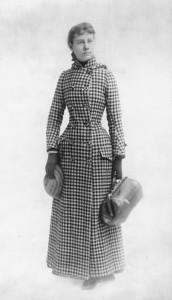 Nellie Bly con su abrigo y la maleta de mano que llevó consigo para el viaje de 72 días.