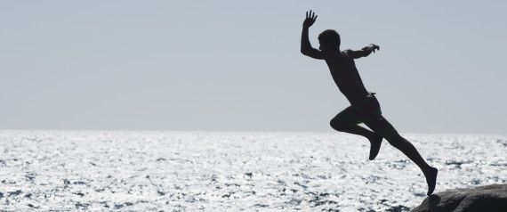 Teenage boy jumping into ocean, silhouette