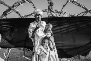 """El refugiado de Mali, de 65 años, con sus hijos en el campo de refugiados de Mentao. Huyó de Mali después de enterarse de que la retirada del ejército llevaría represalias contra los tuaregs a medida que avanzara hacia el sur después de su derrota a principios del 2012. Omar era curandero y maestro de Corán en su pueblo, y era muy respetado. Lo más importante que se llevó es su reloj digital. Dice que un verdadero líder respetable debe garantizar el tiempo. """"El respeto por el tiempo -dice- me hace bueno en lo que hago, y por tanto, un líder respetado"""". Foto © Brian Sokol. ACNUR"""