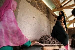 Mujeres reparando su hogar en Pakistán. © ONU-Hábitat