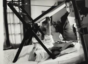 Frida Kahlo pinta en su cama en compañía del artista Miguel Covarrubias, 1940. Puede verse el caballete especial que usaba. Archivo fotográfico del Museo Frida Kahlo.